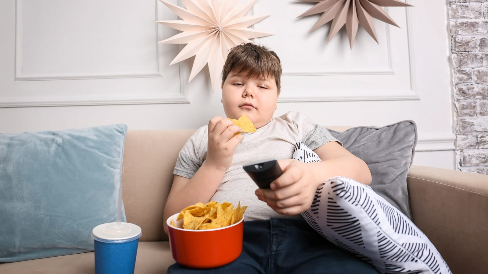 An obese child eating chips