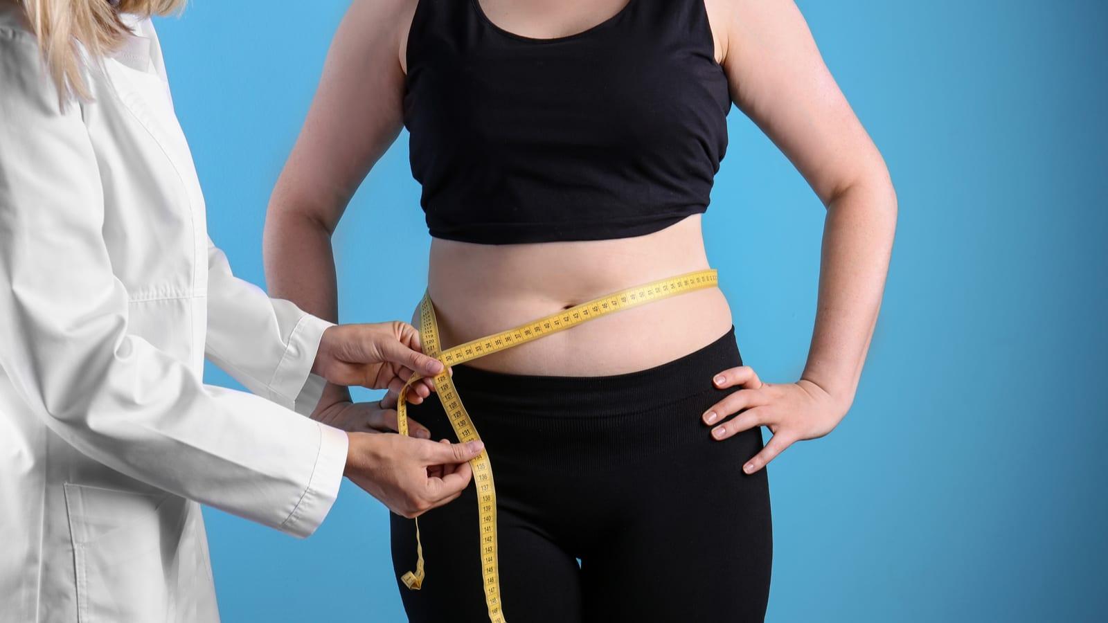Doctor taking woman's waist measurement