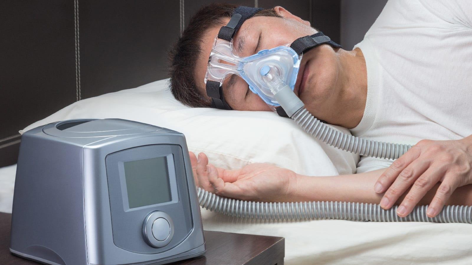 Man asleep with CPAP machine